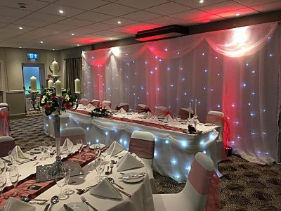 Twinkling_backdrop_led_uplighting_top_table_skirt_centre_pieces_swags_chair_covers.JPG