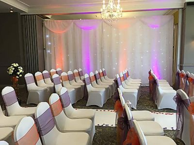 starlight-twinkling-curtain-ceremony-asile-carpet-chair-covers-sashes-rose-trees-petals.JPG