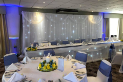 twinkling-backdrop-uplighting-blue-yellow-centrepieces-chair-covers-sashes