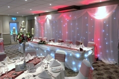 A-Twinkling_backdrop_led_uplighting_top_table_skirt_centre_pieces_swags_chair_covers