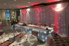 Twinkling_backdrop_led_uplighting_top_table_skirt_centre_pieces_swags_chair_covers