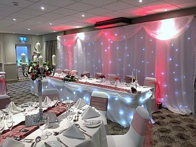 A-Twinkling_backdrop_led_uplighting_top_table_skirt_centre_pieces_swags_chair_covers.JPG