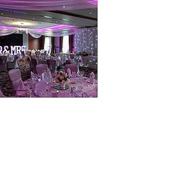 twinkling-backdrop-wedding-venue-dressing-wedding-breakfast-chair-covers-sashes-top-table-cake-table-skirts-swagging-uplighting-mr-and-mrs-letters.jpg