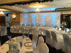 winter_weddings_twinkling_backdrops_star_curtain_uplighting_Top_table_skirt